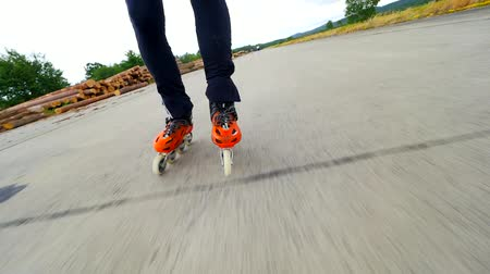 inline skating : Man legs skating on concrete aerodrome surface. Hradcany airport, 9th of July 2019. Inline skating. Close up view of orange hard shell inline boots Stock Footage