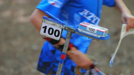 trail marker : Three sportsmen with control chips run at checkpoint with number one hundred. Orienteering race. Stock Footage
