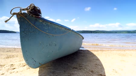 rowboat : Low angle view of anchored laminate blue rowing boat on a large lake with smooth water level. Stock Footage