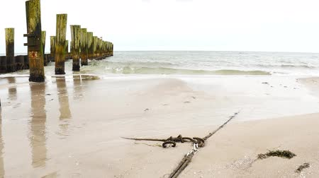 Ocean coast line with anchore rope and wooden poles on a beach
