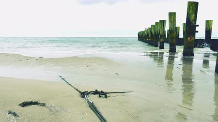 Anchor rope lost in beach sand. Weathered wooden poles of water with splashing sea water