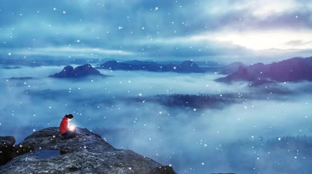 Woman hold lantern of life. Magical Milky Misty Landscape. Woman sit on mountain top with bright star in hands. Gentle snowing or raining, realy cold weather Stock Footage