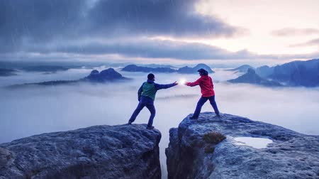 A couple of hikers lovers hold the high above danger gulch between rocks while danger lightning. Night photo in rainy mountains. Valentine lovers standing on rocky mountain peak