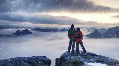 Happy lovers traveling together. Couple reaching for mountain peak while gentle snowing, watch lovely purple sunrise at horizon Stock Footage