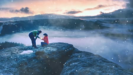 Woman showing lightning lamp to man. Couple while snowing sunrise on summit above valley full of heavy mist. Instagram style stock image