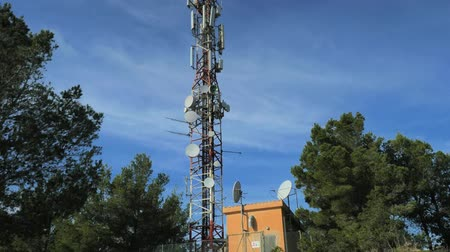 Modern tower with huge complex of telecommunication antennas on old bricks house hidden in pine trees. Mountain trail over Pintal Vermell peak, Majorca island, Spanish Balears islands. Stock Footage