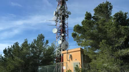 Remote mountain communications center with antennas on steel tower against a deep blue sky.