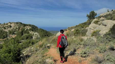 Woman backpacker hiking during mountain trek on Mallorca islan. Sunny spring day with comfortable temperature. Rocky sandy footpath, pine trees, bushes and palms around.