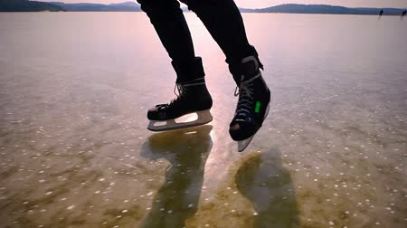 Male feet ice skating in ice hockey iceskates on clear ice of lake. Icy skating in nature. Stock Footage