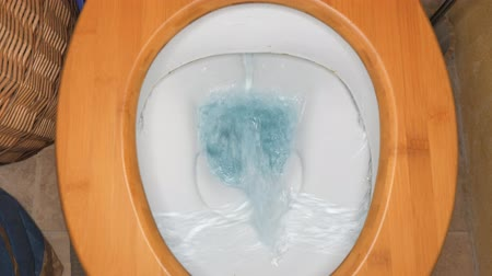 White toilet bowl in flat room. Flushing white toilet. The blue water swirls in the toilet bowl