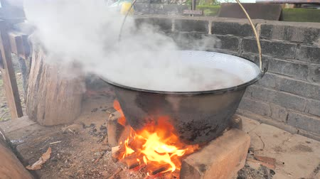 caldo : The cook with gloves removes the people from the boiler with pork and bones. Outdoor cooking in pot over campfire.