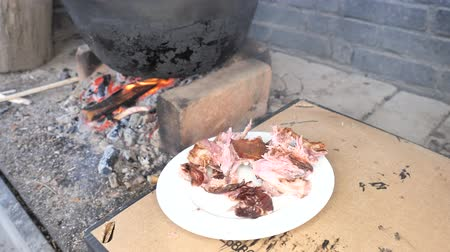 Male wrists and fingers break off meat from bones of boiled pork on white plate. Tasting during the preparation of an excellent dinner party.