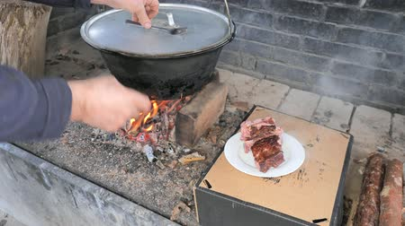 gulasz : Chef with fork and plate takes out cooked ribs from a steaming pot. Cooking of traditional delicatessen for party on open fire.