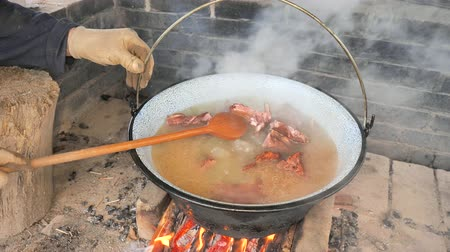 Mixing soup with wooden spoon in kettle. Mixing cooked meat and bones on an open fire. Stock Footage