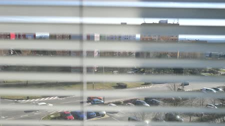 щит : Window view through the blinds at the street through the blinds. Town street through silver window blinds close up.