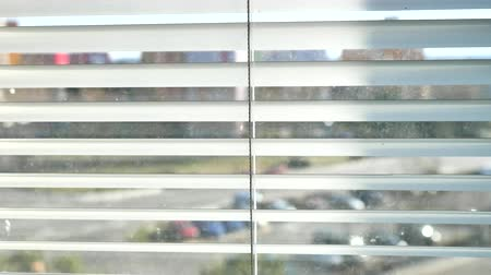 Town street through silver window blinds. Movement on street between flat houses through window open blinds. Stock Footage