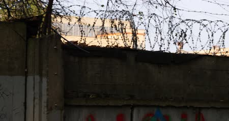 płot : Panning shot of a razor wire topped metal fence being shaken as if by a prisoner who wants to get out.