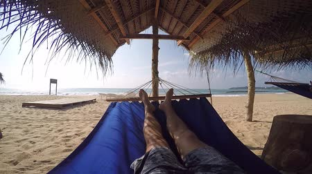гамак : pov man in hammock in the shade of palmtrees on tropical beach