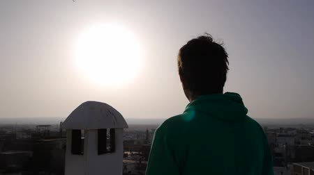 arka görünüm : Back view of young man looking at sunset, medina, morocco Stok Video