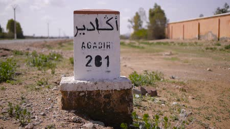 marrocos : Closeup of distance sign road to Agadir written in French and Arabic languages with carriding in the background. Morocco Vídeos