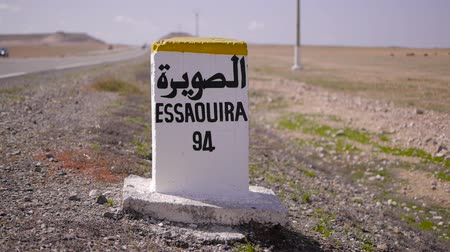 filho : Closeup of distance sign road to essaouira  written in French and Arabic languages with carriding in the background. Morocco Vídeos