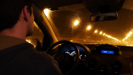 trabalho : Interior view of a man driving his private taxi through the city streets at night