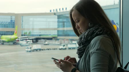 busy line : Woman using smart phone by the window at the airport, plane in background Stock Footage
