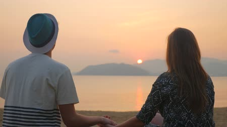 arka görünüm : Back view of young man holding his girlfriends hand. Couple sitting at the beach and watching the sunset over the sea. Tropical vacation in Vietnam. Stok Video