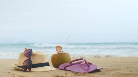 релаксация : flip flops, sunglasses and straw hats on the beach. Relax concept (copy space) Стоковые видеозаписи