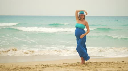 maternidade : Young pregnant woman in beautiful dress at the sand beach posing to a camera. Vídeos