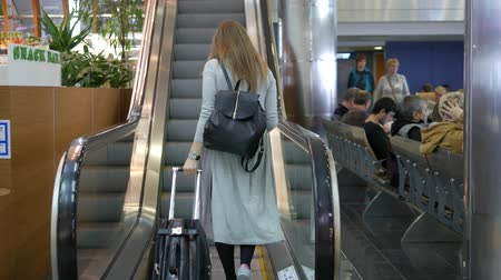 walk behind : Woman with suitcase and rucksack rises on escalator in airport