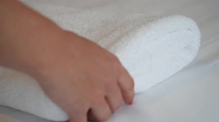 çamaşırhane : Close up shot of female hands putting fresh clean towel on the bed with white sheet