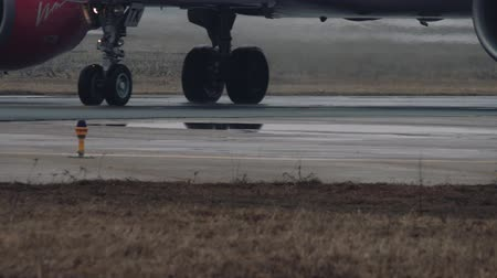 pist : Wheels and turbines of an airbus a320 moving on a runway in the airport. Close up view, Fog weather, 4k UHD 2160p