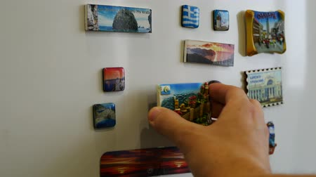 hűtőgép : A new fridge magnet from the last vacation, travel concept Stock mozgókép