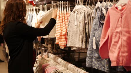 clothing : Pregnant woman choosing Baby Clothing in baby and maternity shop