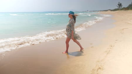opalenizna : Smiling pregnant woman walking on a beach in swimwear, tunic and blue hat