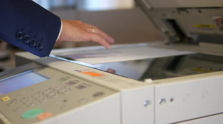 duplication : Man opening the lid of an office copier and putting a document for making a copy. Dolly shot
