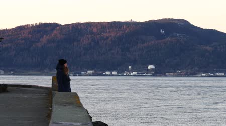 trondheim : Caucasian woman standin near sea quay and waiting for sunset. Trondheim fjord, Norway.