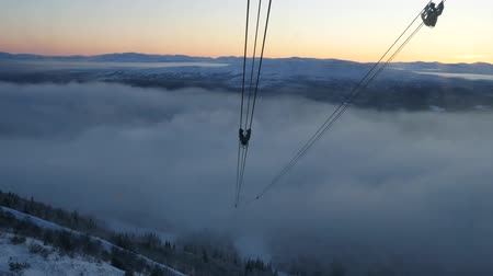 chairlift : View from moving cabin on oncoming tower of cable car and setting sun. Sweden Stock Footage