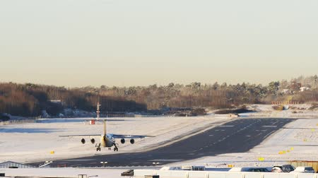 homecoming : 4k footage airplane landing in winter airport, dawn sunrise time