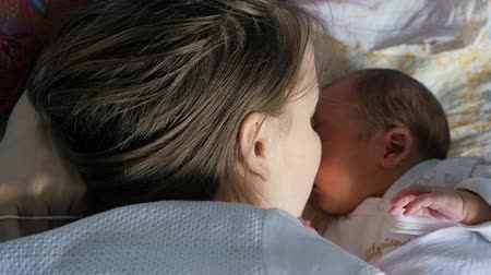 драгоценный : Happy woman kissing her newborn son in a bed