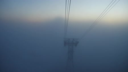 downwards : View from a cabin to a cable car tower appearing from the fog. Low visibility at mist