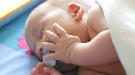 slumber : Close up portrait of a caucasian baby sleeping with a dummy Stock Footage
