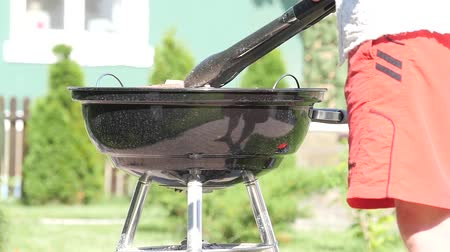 tongs : Man roasting meat on a charcoal grill. Handheld shot Stock Footage