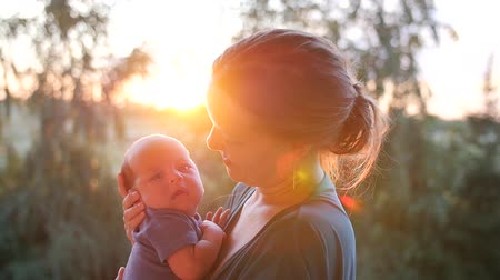 narozený : Young mother with a baby in her arms in rays of setting sun. Handheld shot
