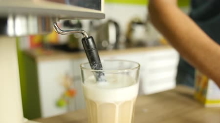 chrom : Making cappuccino: preparing hot milk foam and pouring coffee in it