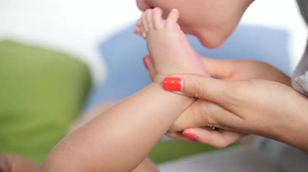 barefooted : Close up of woman kissing bare feet of a newborn baby. Handheld shot Stock Footage