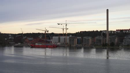 moorage : Floating on the river by buildings, tower cranes and red ship
