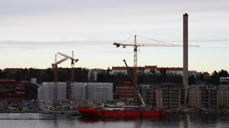 construction crane : Moving by the shore with cinstruction site and buildings Stock Footage