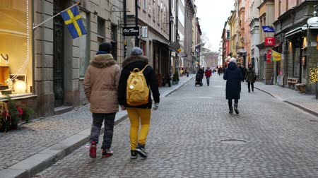 stockholm : Tourists walking on Stockholm street. Handheld shot, camera moves from street to the top of the building Stock Footage